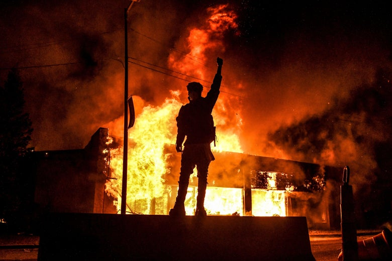 A protester stands in front of a burning in Minneapolis.