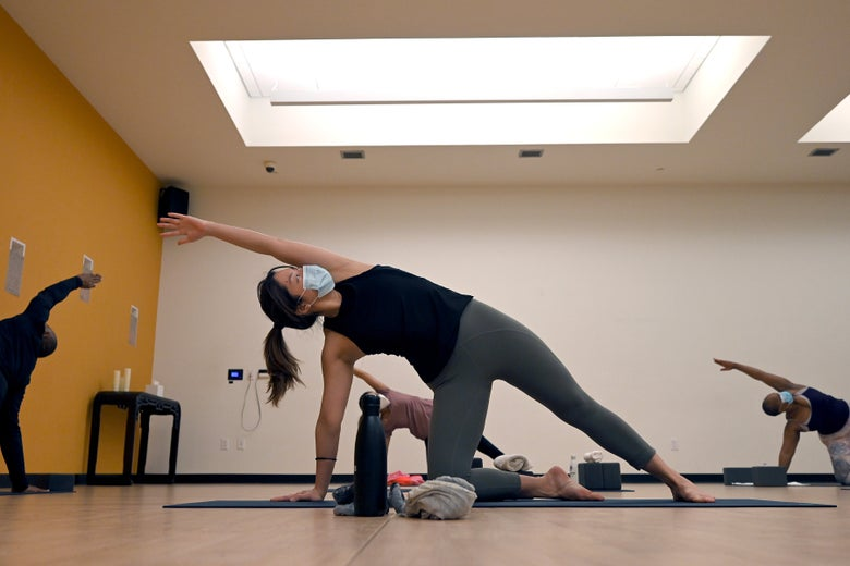 A woman lifts her arm over her head in a yoga pose in a class with others doing the same pose in the background.