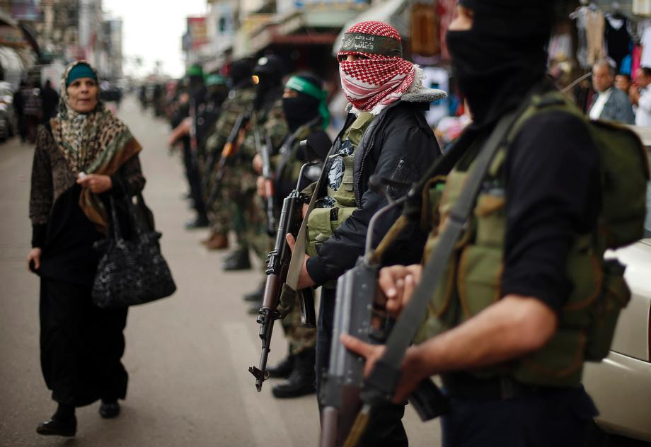 A Palestinian woman walks past Hamas militants as they take part in the funeral of Hamas female lawmaker Mariam Farahat in Gaza City on March 17, 2013.