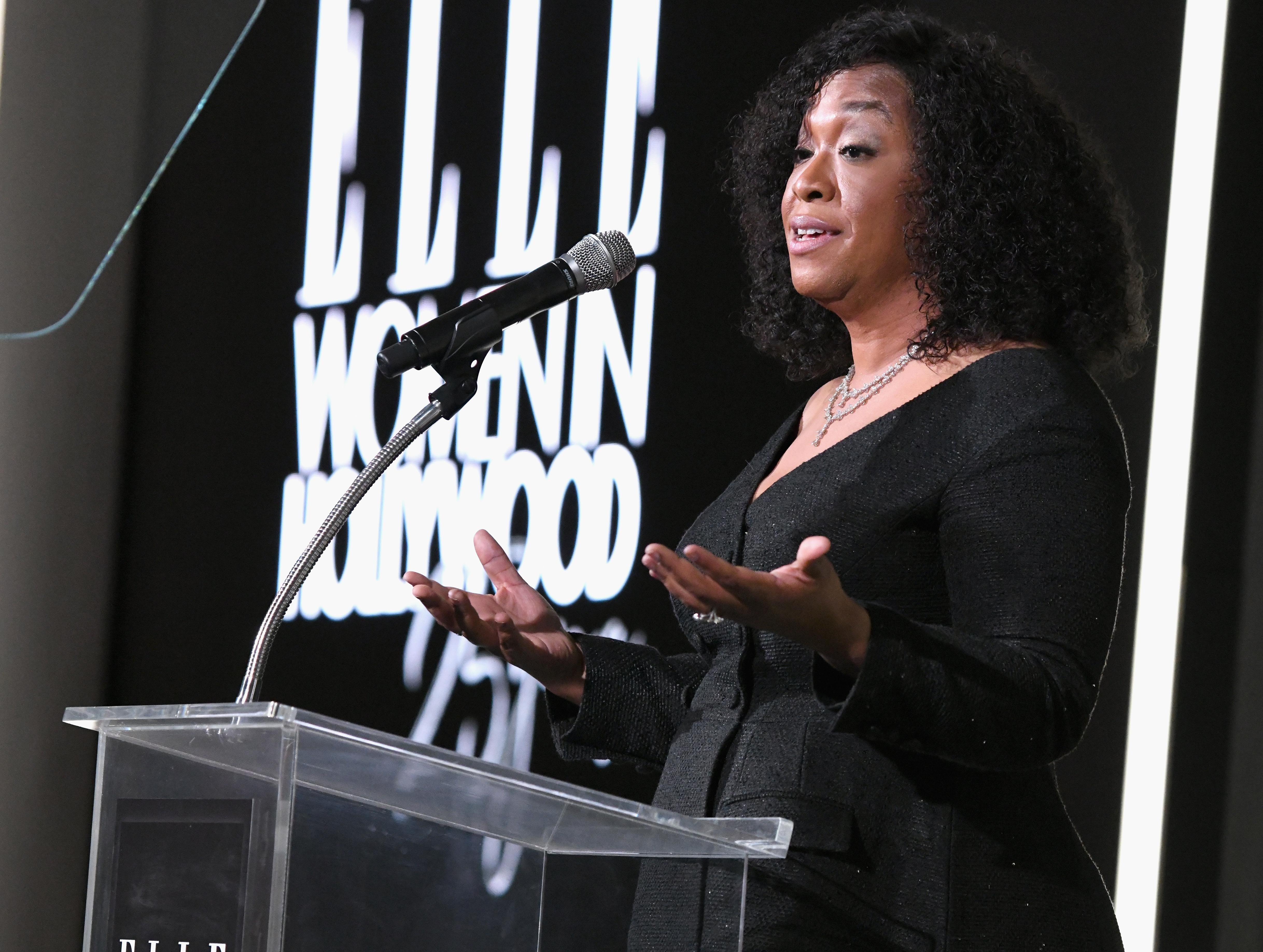 Shonda Rhimes stands at a glass podium, arms outstretched.