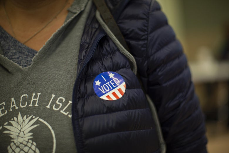 A woman wears a sticker after casting her vote at a polling station.