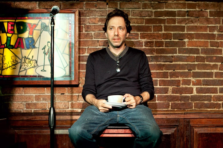 Noam Dworman seated onstage at the Comedy Cellar.