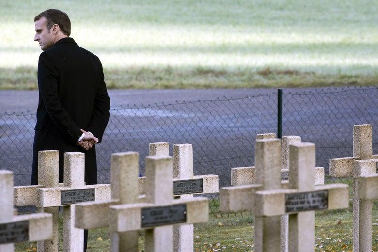 Emmanuel Macron standing among graves.