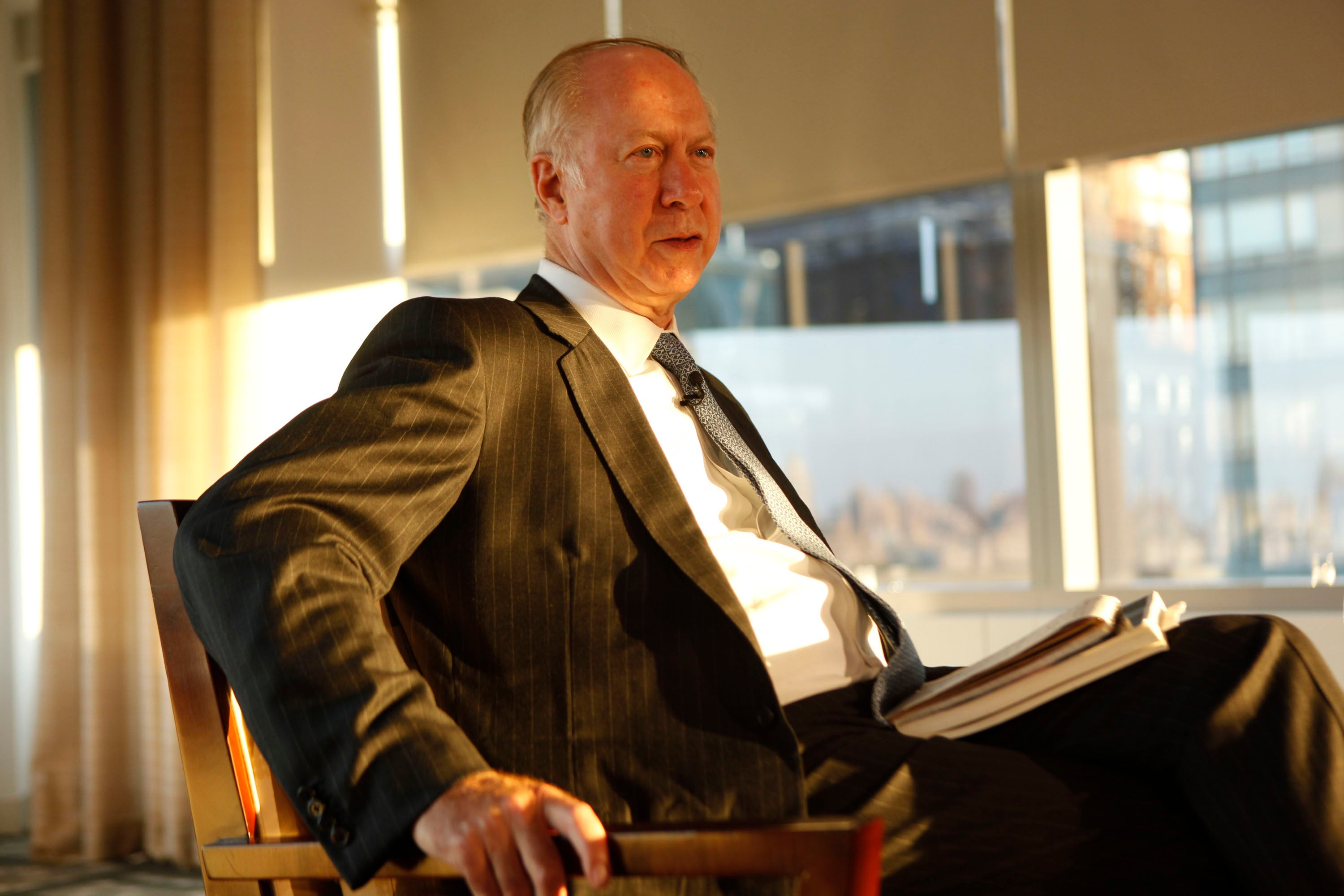 Gergen, wearing a suit, is seated in a chair in a sunny room.