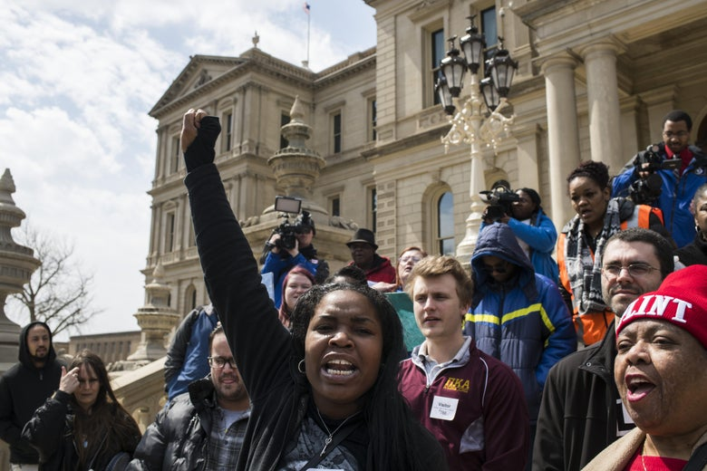 Protesters hold up their fists and chant on the steps of the Michigan state Capitol.