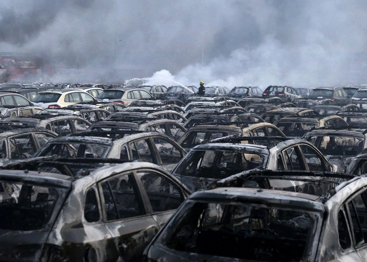 A firefighter works at the site near damaged vehicles as smoke rises from the debris after the explosions at the Binhai new district in Tianjin, China.