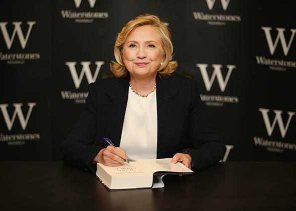 Former US Secretary of State Hillary Clinton signs copies of her