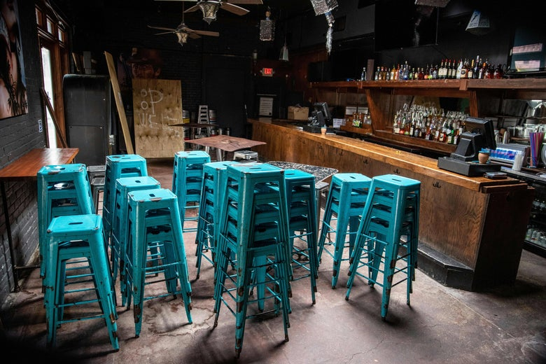 Chairs sit stacked inside a closed bar.