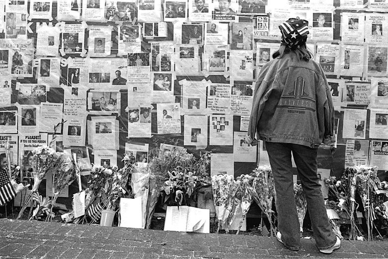 A young woman looks at one of the many displays with photos of the missing on a wall.