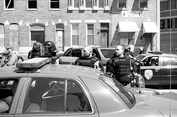 Three police officers look in the direction of a noise from down the street. It was nothing in particular. Baltimore.