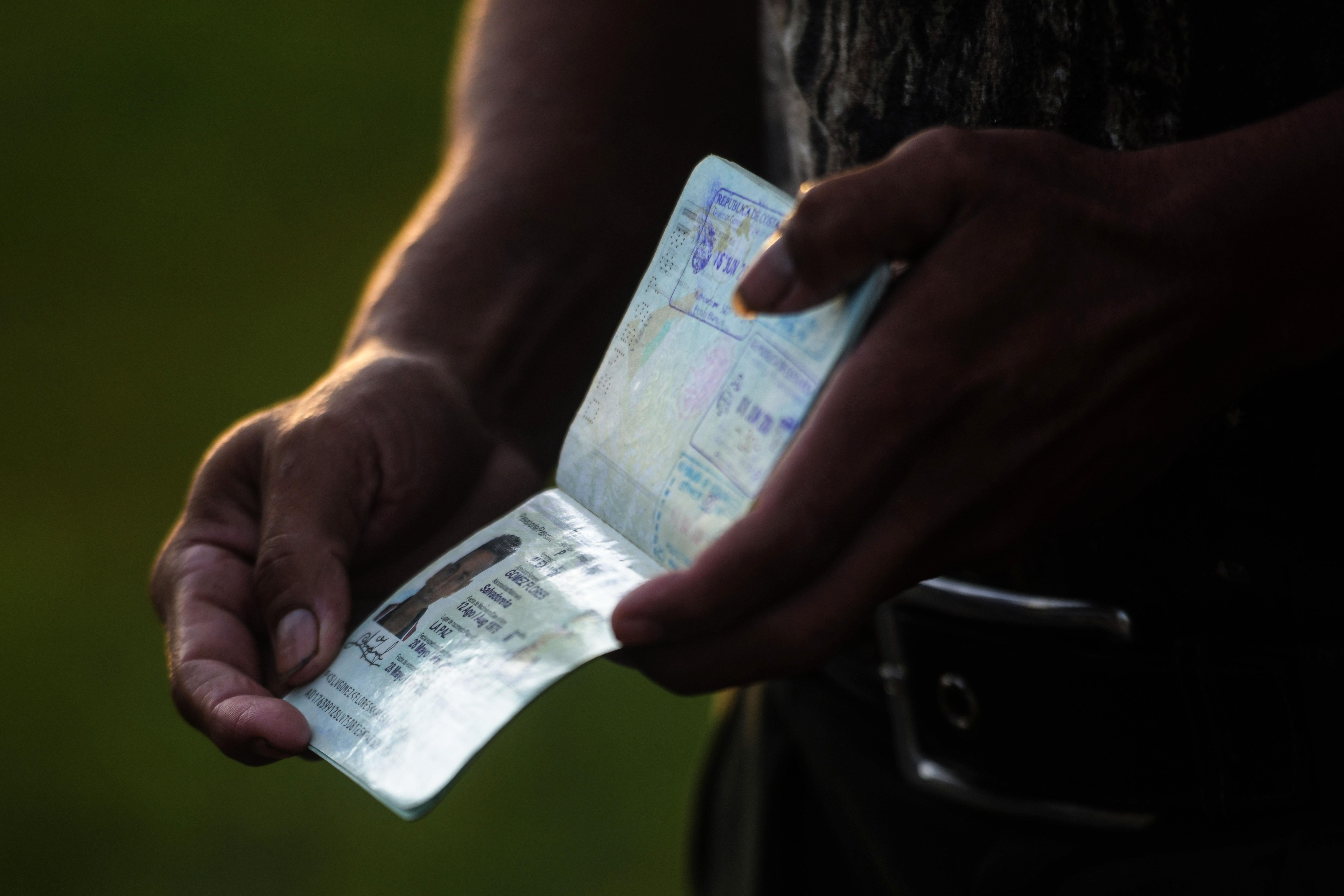 A Salvadoran migrant shows his passport as he gathers in a caravan in San Salvador to start a journey towards the U.S. on Oct. 28, 2018.