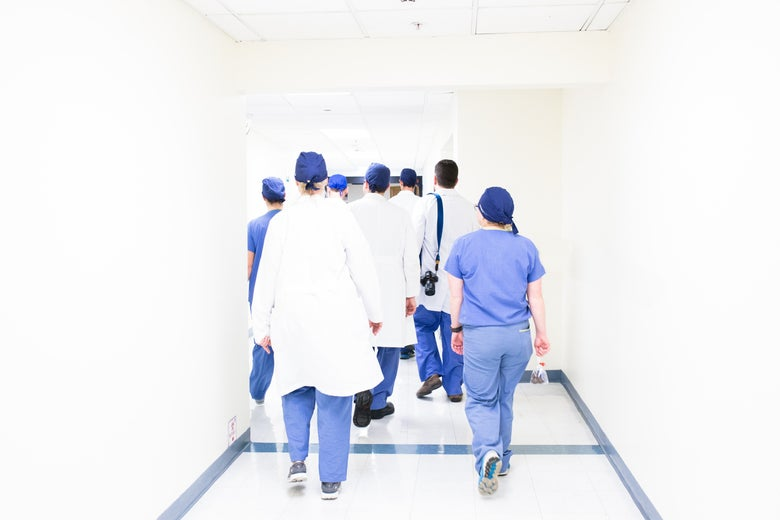 Doctors walking down a hallway with their backs turned.