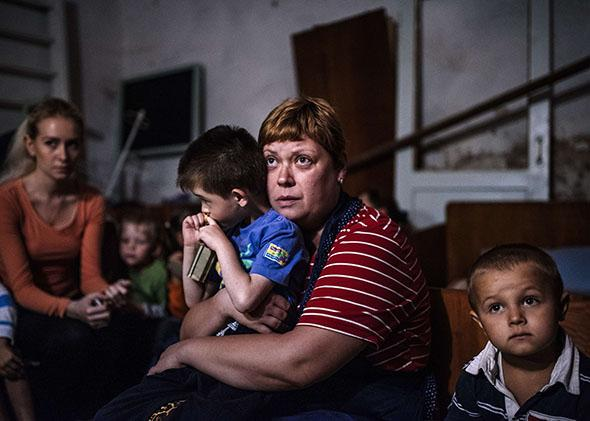 Children and their educators hide in a bomb shelter in an orphanage during a shelling in the town of Makiyivka on August 19, 2014.