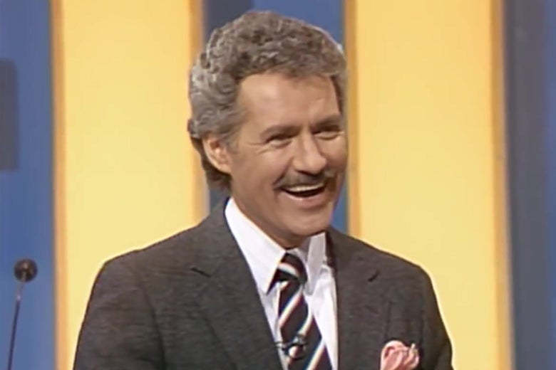 Alex Trebek, circa the 1980s, smiling broadly on the set of Jeopardy.