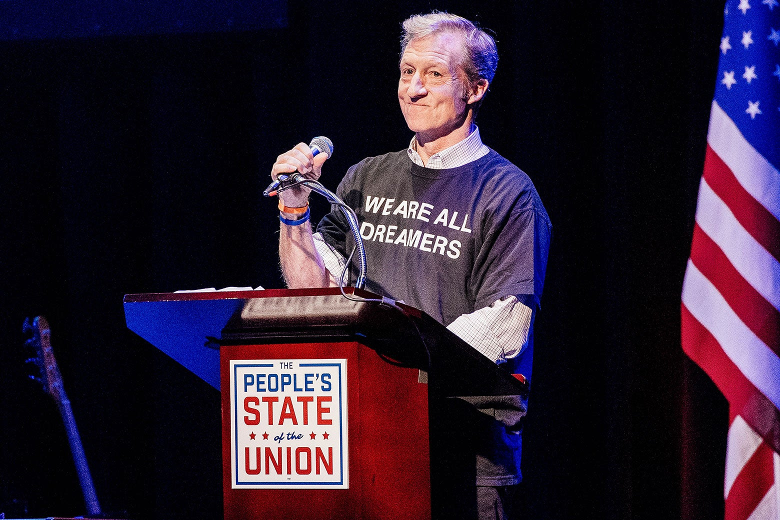"""Tom Steyer, wearing a shirt that says, """"We are all Dreamers,"""" stands at a podium."""