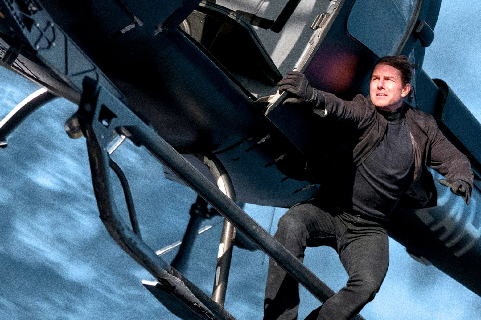 Tom Cruise attempting to hold fast to the outside of a helicopter in Mission: Impossible - Fallout.