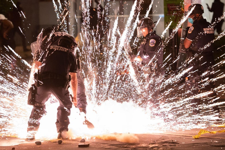 A firecracker thrown by protesters explodes under police one block from the White House on May 30, 2020 in Washington, D.C.