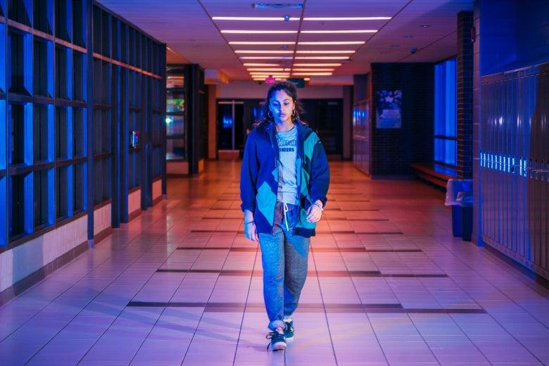 Rhianne Barreto walks down a hallway lined with lockers.