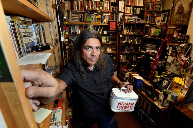 """Stephen Graham Jones stands in a room full of books, carrying a box labeled """"Human Organ."""""""