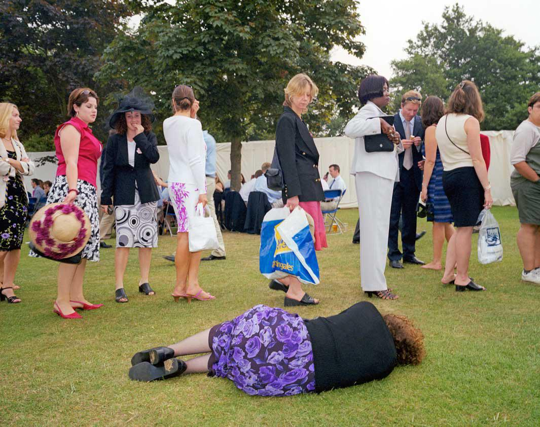A woman lies on the grass next to a queue for the toilet at the Henley Royal Regatta.