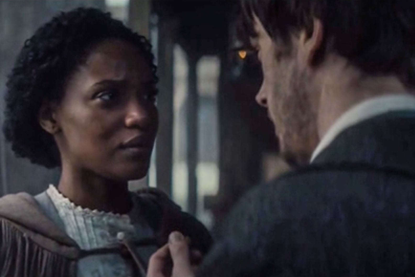 In a 19th-century setting, a white man talks to a black woman who is wearing a cloak and looks worried.