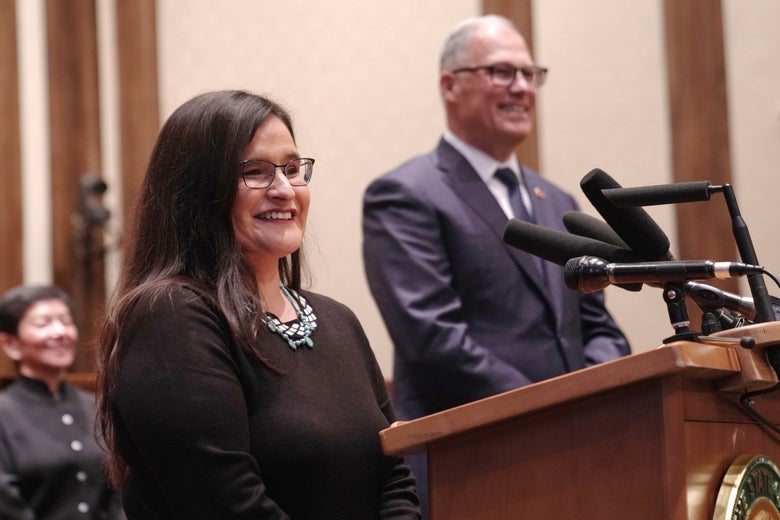 Raquel Montoya-Lewis smiles, standing at a podium next to Jay Inslee as he announces her appointment at a formal ceremony.