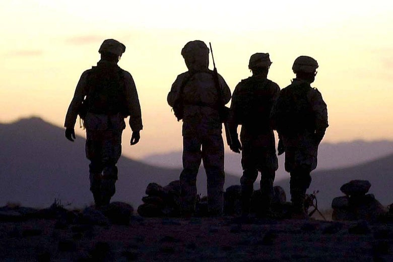 U.S. soldiers in silhouette on a hilltop in Afghanistan.