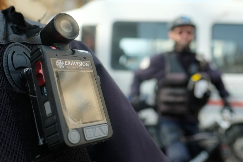 A police officer stands guard with a body camera attached to the shoulder.