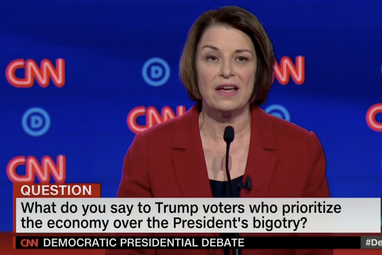 "In this screengrab from CNN, Amy Klobuchar debates. The banner reads: ""What do you say to Trump voters who prioritize the economy over the President's bigotry?"""