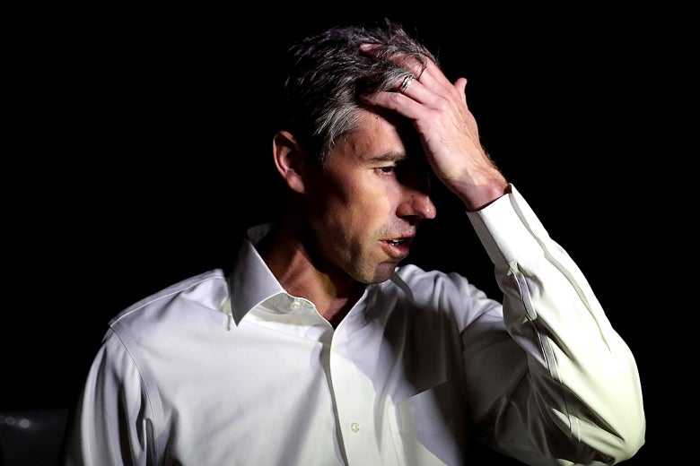 Beto O'Rourke holds a hand to his forehead while he talks with reporters after a day of door-to-door canvassing on Nov. 3 in Dallas.