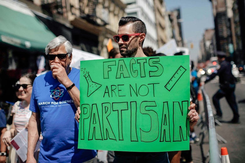 A man carrying a poster reading Facts are not Partisan at a march in New York City.