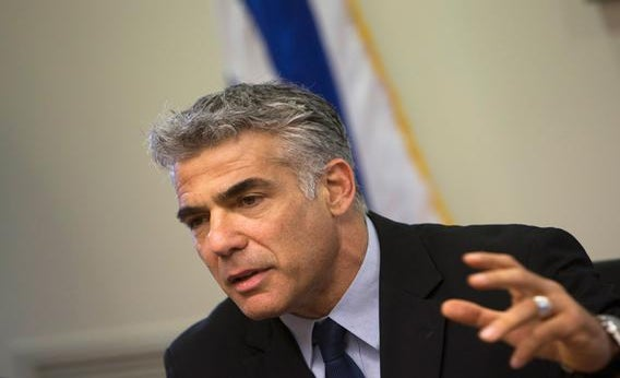 Israel's Finance Minister Yair Lapid gestures as he speaks during a Yesh Atid party meeting at the Knesset, the Israeli parliament, in Jerusalem, May 20, 2013.