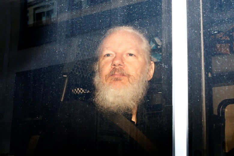 Julian Assange, bearded, seen through a van window.