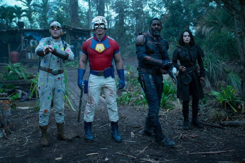 In a forest, a man wearing a crudely made polka dot-covered jumpsuit, a man in a bright red shirt and a metal helmet, and a man and woman both wearing all black.