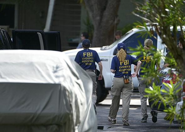 FBI personnel walk through the complex surrounding the apartment