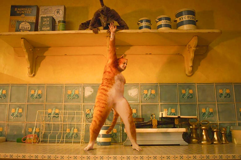 Rebel Wilson, wearing a yellow cat suit with a white belly, stands on a kitchen counter with a floral tile backsplash, one arm reaching up toward a shelf with boxes and jars.