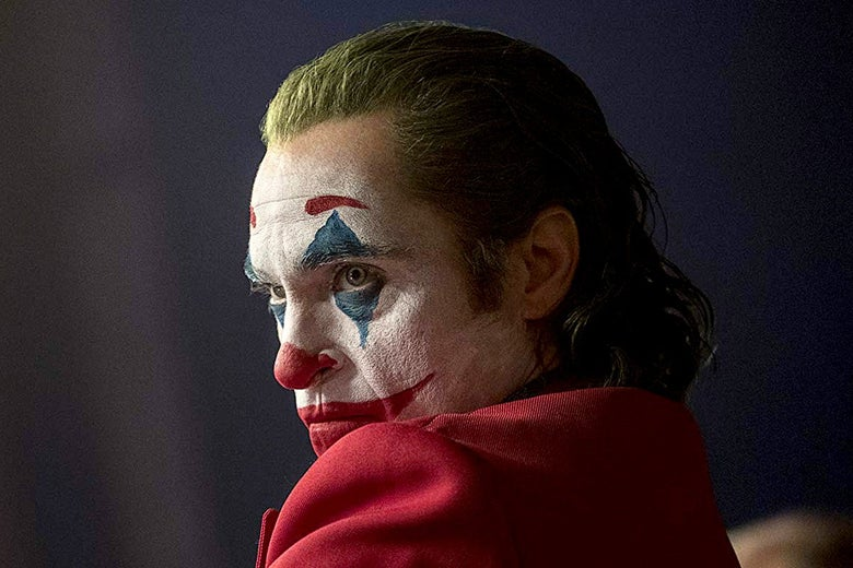 Joaquin Phoenix, in profile, in a red suit and clown makeup.