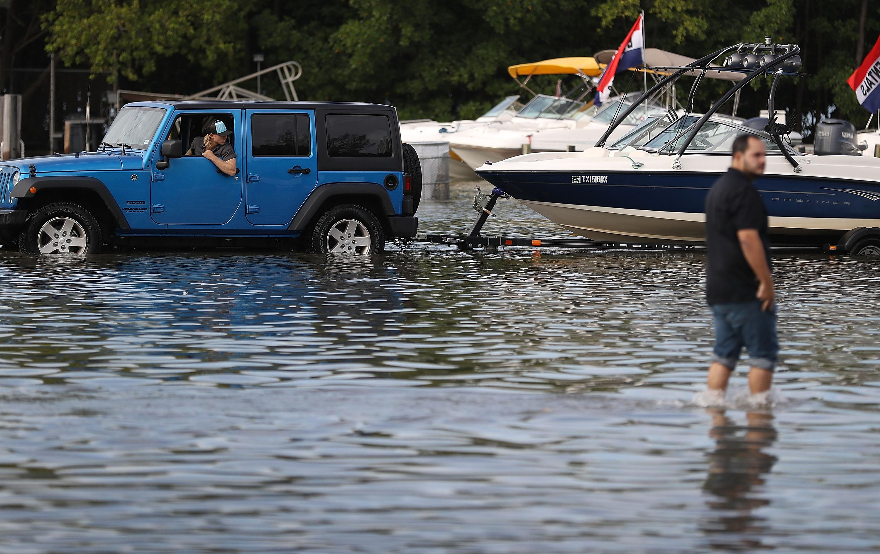A man drives through a flooded parking lot to put his boat in at a ramp.