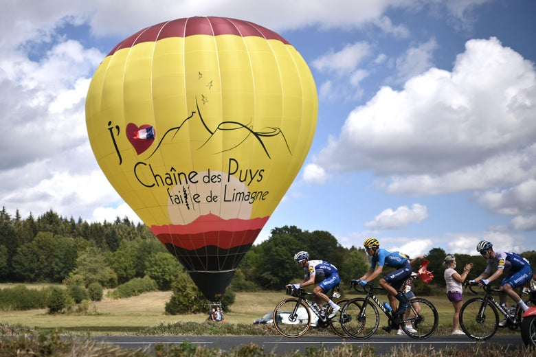 Three cyclists racing in the Tour de France on a quaint country road, in front of a hot air balloon.