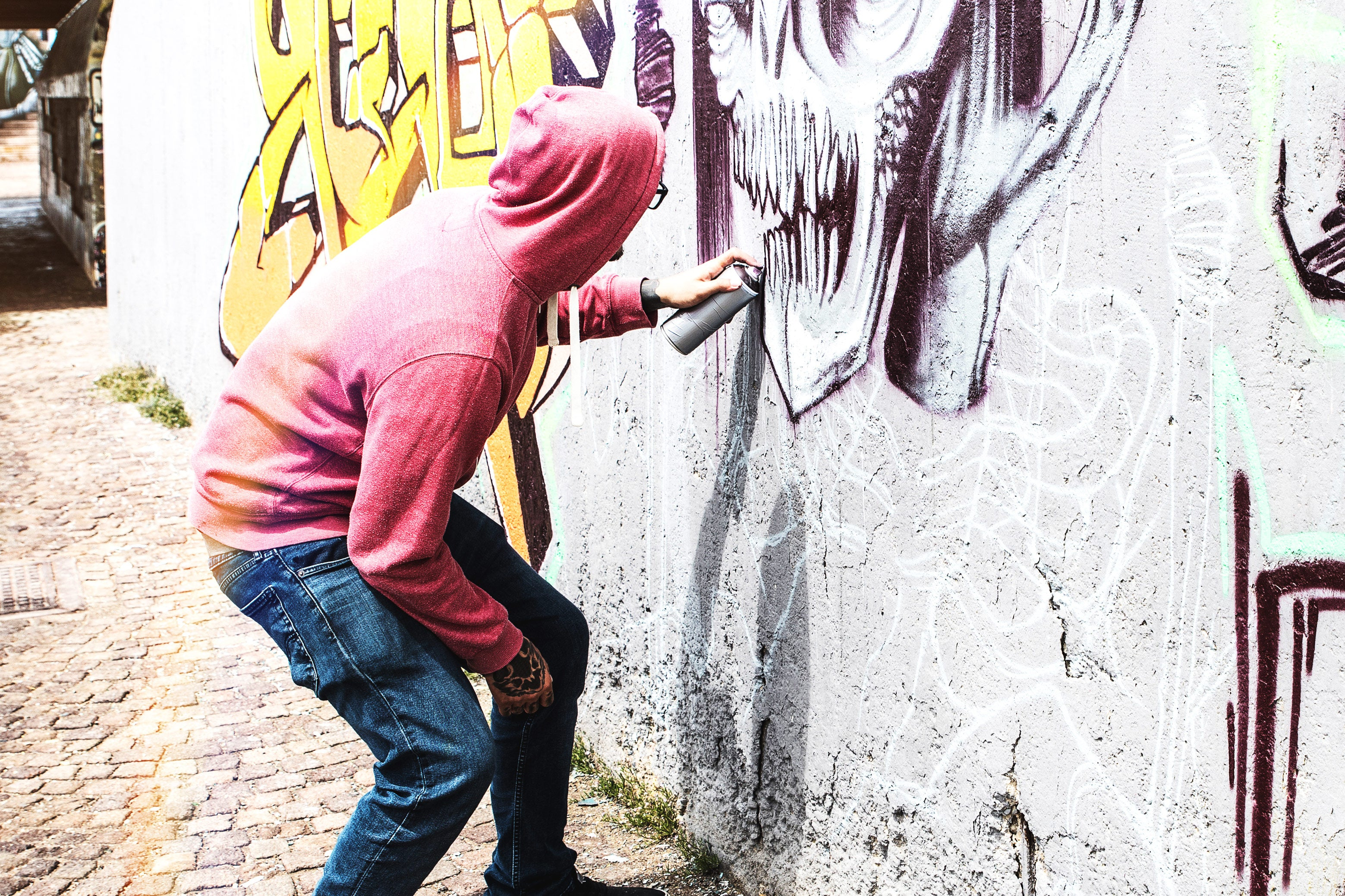 Street artist painting colorful graffiti on public wall with multi-color aerosol spray. The artist is not Kyle.