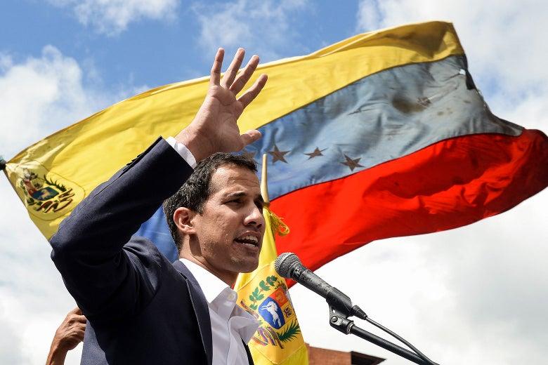 Juan Guaidó speaks in front of a Venezuelan flag.