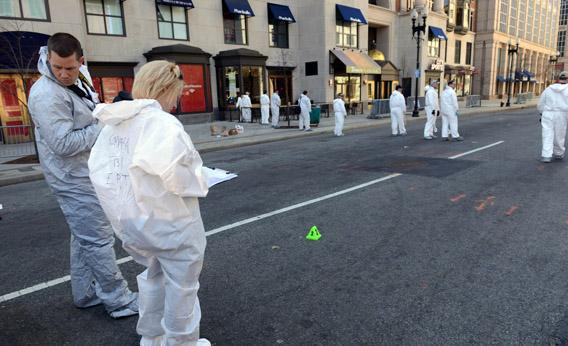 FBI crime scene investigators stand near an evidence marker on Boylston Street just past Berkeley Street as they sweep up towards the bomb scene of the Boston Marathon.