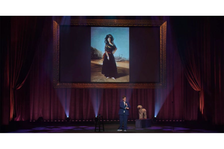Hannah Gadsby on stage, in front of a projection of a Goya painting of a woman in a black dress and white shoes.