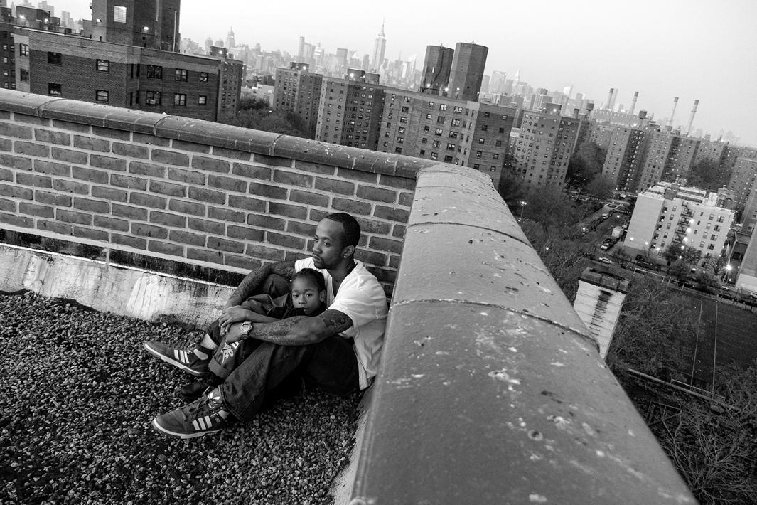 New York, New York, 2013. Jerell Willis and son Fidel on the rooftop of their apartment building.