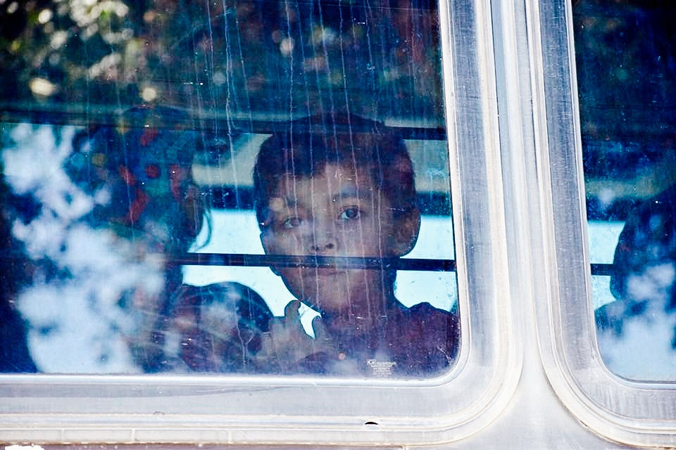 A child looks through the window of a bus carrying migrants near McAllen, Texas, on Saturday.