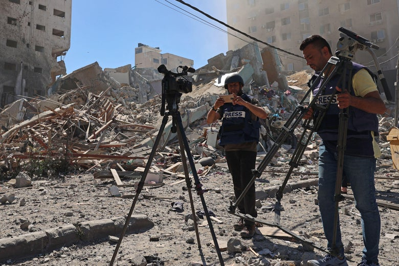 Journalists stand next to the rubble of Jala Tower, which housed international press offices, following an Israeli airstrike in the Gaza Strip on May 15, 2021.