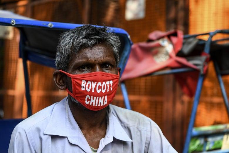 """A rickshaw driver wears a face mask saying """"Boycott China."""""""
