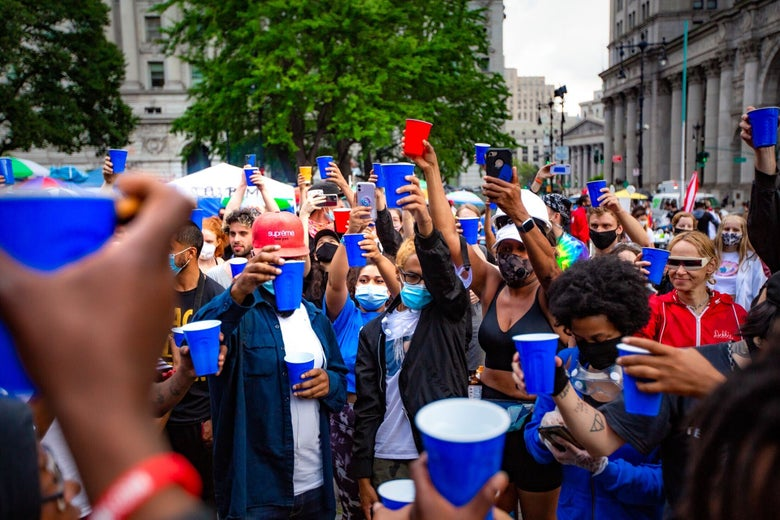 Protesters raise red and blue plastic cups in a toast at Occupy City Hall
