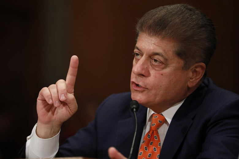 Napolitano, seated, points as he speaks in front of a mic at a hearing