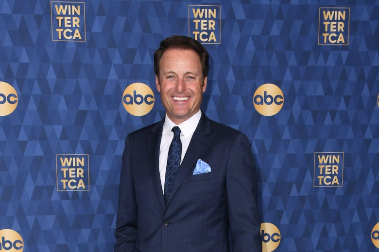 Chris Harrison in a suit standing in front of an ABC step and repeat.